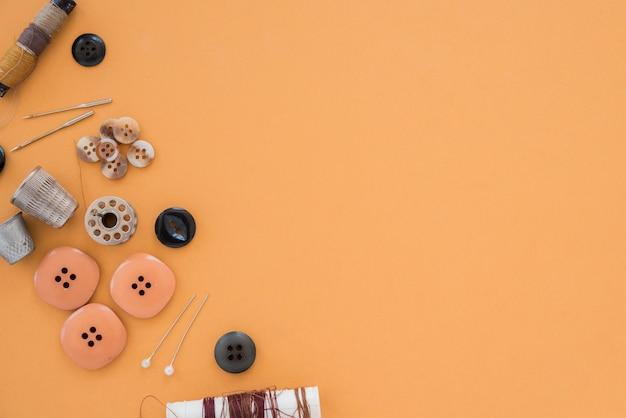 Нить; кнопки; иглы; наперсток на цветном фоне