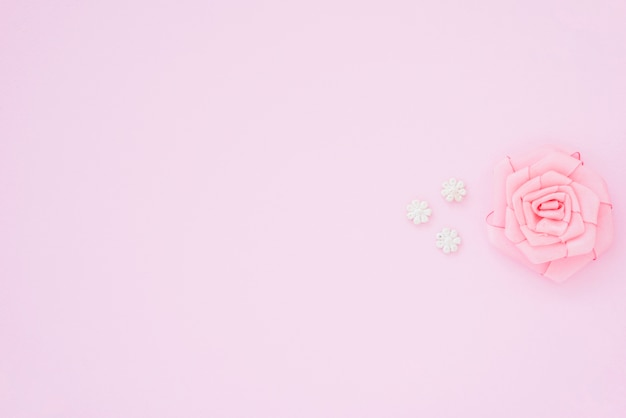 テキストを書くためのスペースとピンクの背景にリボンで作られたピンクのバラ