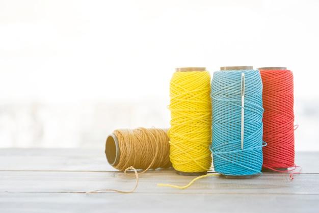 木製の机の上の針でスプール糸の種類