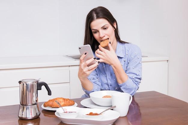 Молодая женщина ест печенье, имея завтрак на кухне