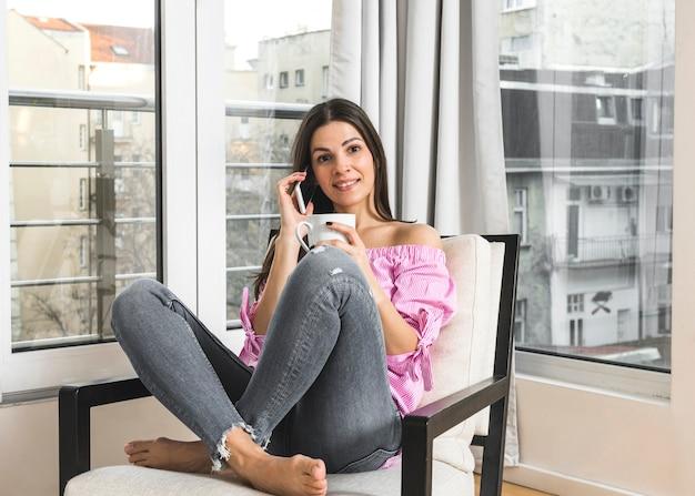 Улыбается молодая женщина, сидя на стуле, разговаривает по мобильному телефону с чашкой кофе в руке