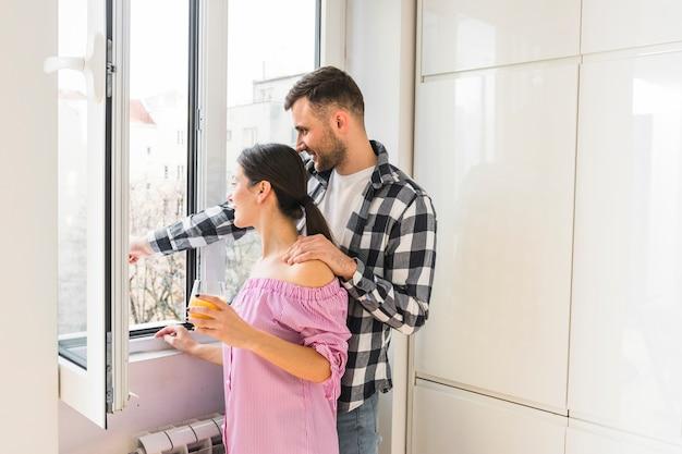 若いカップルが自宅の窓の外を見て