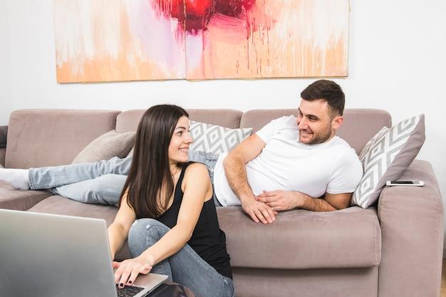 ラップトップを使用して彼女のガールフレンドを見てソファーに横になっている若い男