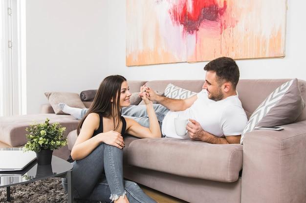 地面に座っている彼のガールフレンドの手を握ってソファーに横になっている若い男