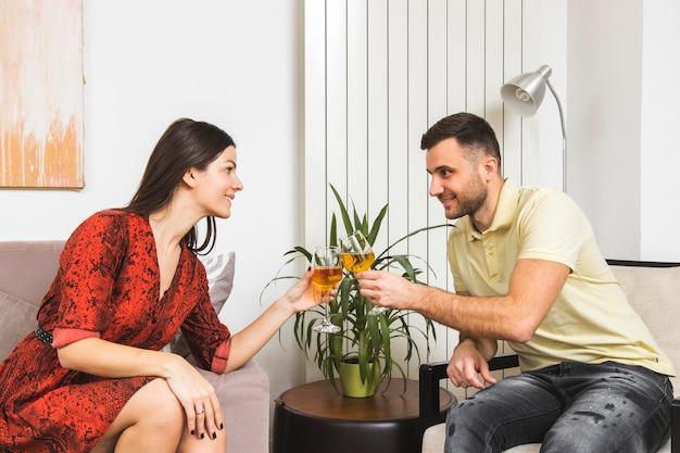 Молодая пара щелкает рюмки сидя лицом к лицу