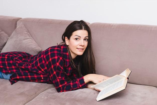 Улыбается молодая женщина, лежа на диване, читая книгу
