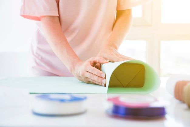 Крупный план женщины, украшающей подарочную коробку декоративной бумагой на столе