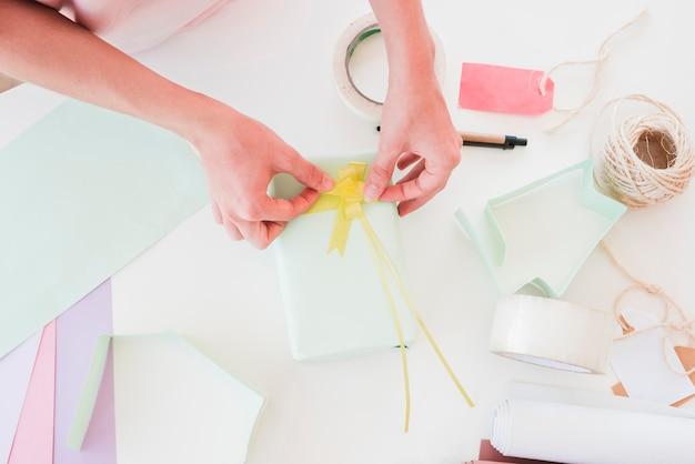 Вид сверху женщины, наклеивающей желтую ленту на упакованную подарочную коробку