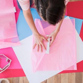 Возвышенный вид женщины, оборачивающей коробку розовой бумагой на карточную бумагу над столом