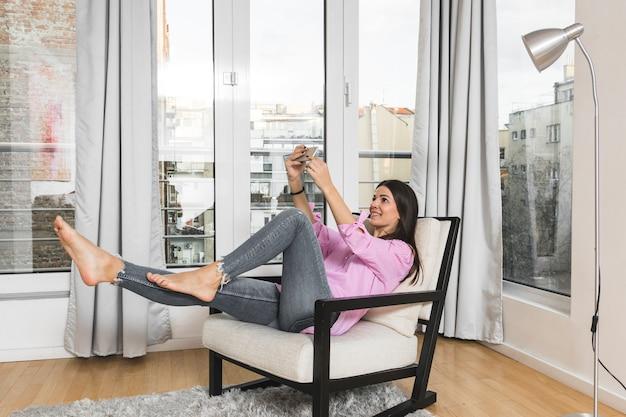Улыбается молодая женщина, принимая селфи на мобильном телефоне у себя дома