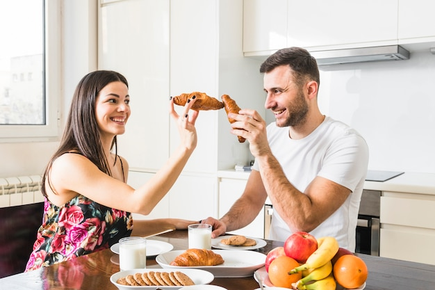 台所でクロワッサンと遊ぶ若い男の笑みを浮かべてください。