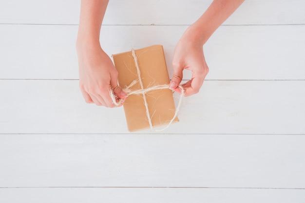 木製の机の上の茶色のラップギフトボックスに糸を結ぶ女のクローズアップ