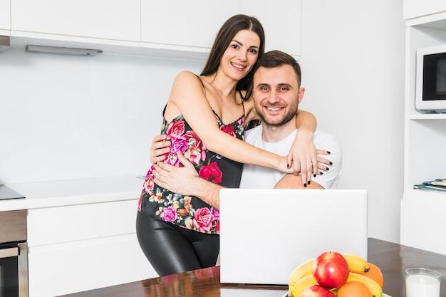 カメラを見て抱きしめる笑顔の愛情のあるカップルの肖像画