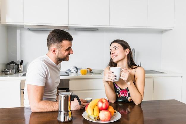 コーヒーを楽しんでキッチンで一緒に座っている若いカップルの笑顔