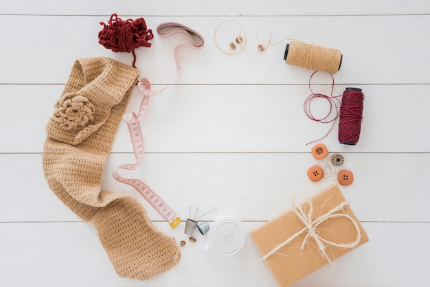 Вязаные чулочно-носочные изделия; шерсть; измерительная лента; золотник; кнопка; обернутая подарочная коробка на деревянном столе