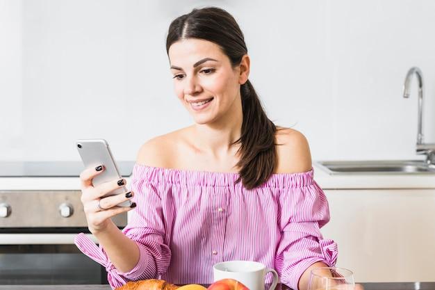 自宅で携帯電話を使用して若い女性の幸せな肖像画