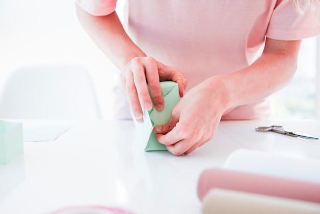 女性の手のデッキの上のギフトボックスに紙を包む