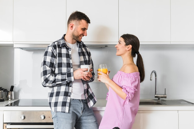 カメラを見てキッチンでコーヒーカップとジュースのガラスの地位を保持している若いカップルの笑顔