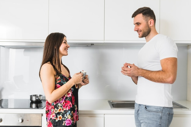 お互いを見て手にコーヒーカップを保持している若いカップルの笑顔