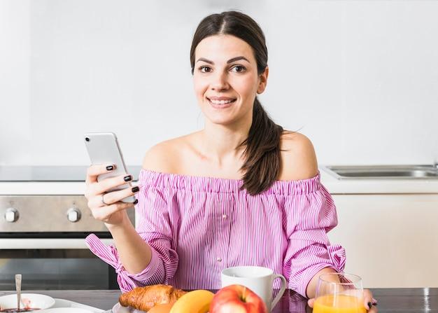 Улыбаясь портрет молодой женщины с помощью мобильного телефона с завтраком на столе