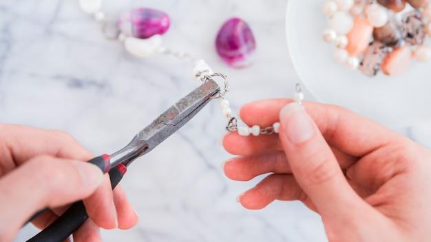 ペンチで金属製のリングを固定する女性の手のクローズアップ