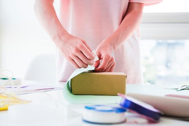 Крупный план женщины, оборачивающей подарочную коробку на столе