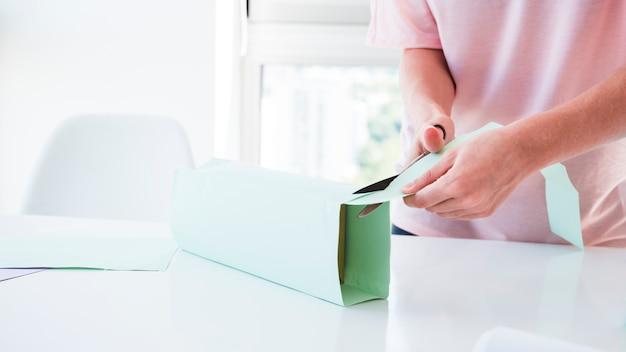 Женская рука режет обернутую на коробке бумагу ножницами