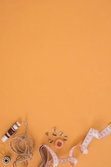 スプール;ジュート文字列。ボタンとオレンジ色の背景にテープを測定します