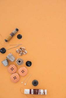 Катушки с нитками; кнопки; иглы; наперсток и кнопка на оранжевом фоне