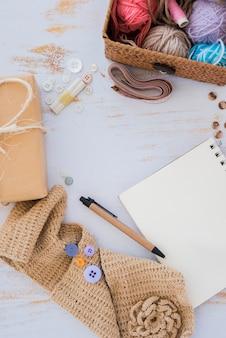 ボタン包まれたギフト用の箱。巻き尺;ペン;ニットスカーフと白い木製のテーブルの上のスパイラルメモ帳