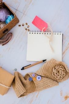 手作りの赤いタグ。スパイラルメモ帳。ペン;ボタンと木製の机の上のバスケットを持つウール