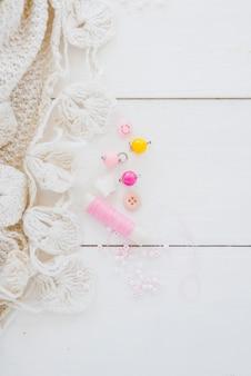 かぎ針編みの白い生地。ビーズと木製の机の上のピンクのスプール