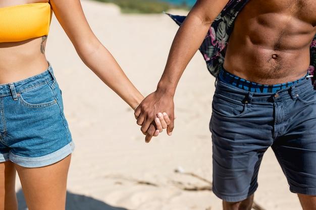砂の上に立って手を繋いでいる多民族のカップル