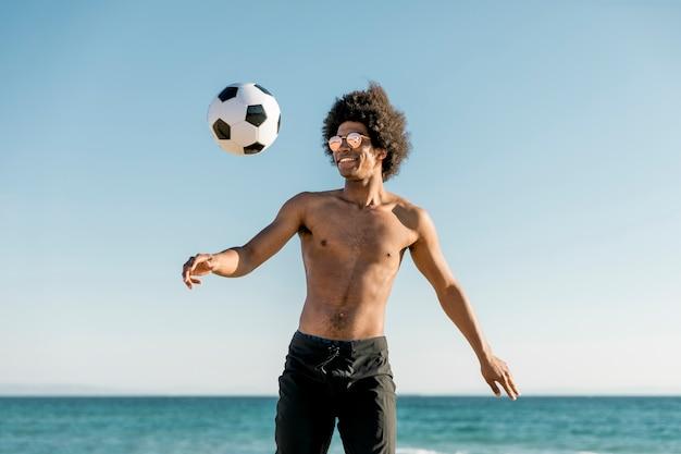 陽気なアフリカ系アメリカ人のスポーツマンが海辺でサッカー