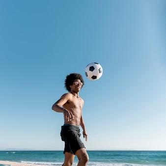 Радостный молодой афроамериканец спортсмен играет в футбол на берегу моря