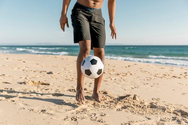 スポーツマンの海岸でボールを打つ