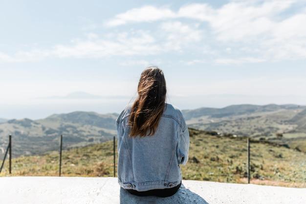 Молодая женщина, наслаждаясь видом на горы