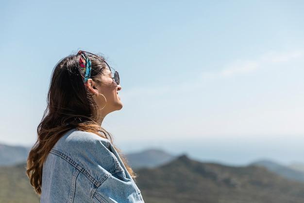 Взрослая женщина в солнечном свете против гор