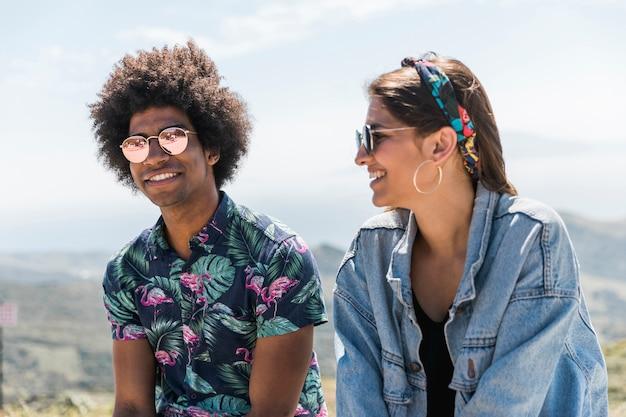 山の上に座って幸せな若いカップル