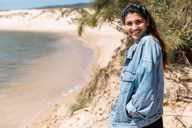 Улыбающиеся молодые девушки стоя на берегу моря