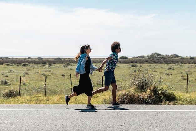 日当たりの良い道路で走っているカップル