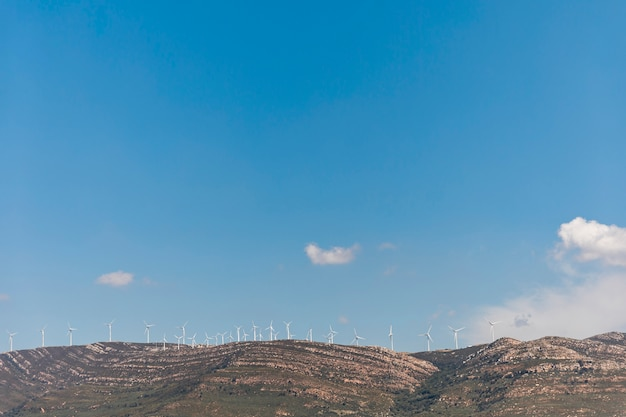 Горы с ветряными мельницами под голубым небом