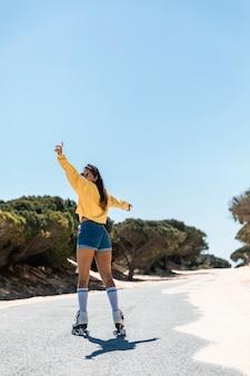 空の道でスケートに乗って若い女性