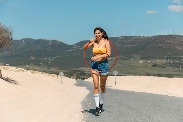 砂の上のフラフープで歩く若い女性