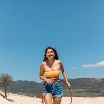 フラフープで走っている若いスリムな女性