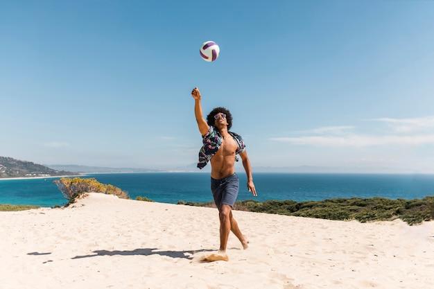 アフリカ系アメリカ人の男がビーチでボールで遊ぶ