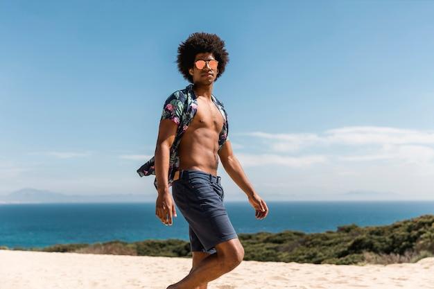 ハンサムなアフリカ系アメリカ人の男がビーチの上を歩いて