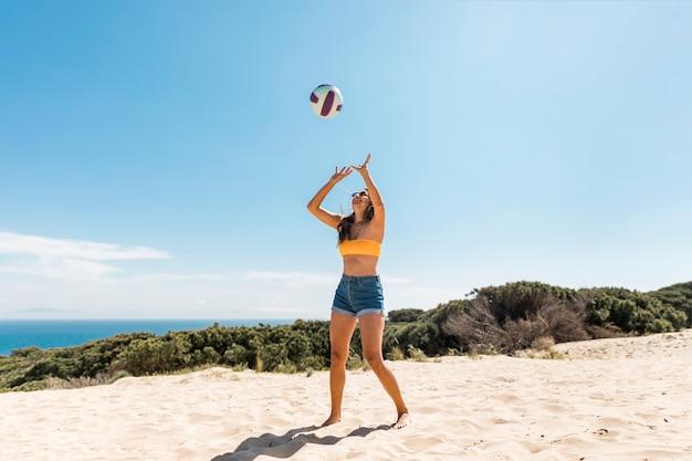 幸せな女がビーチでボールで遊んで
