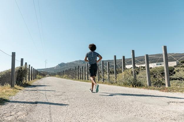 空の田舎道を走っている若い男