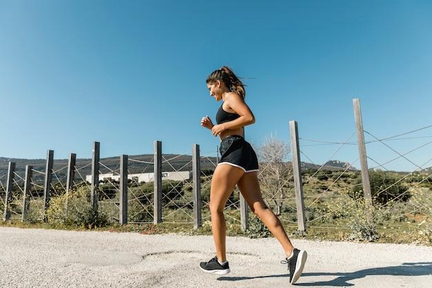 田舎道に沿ってジョギングの若い女性
